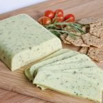 vegan cheese with herbs, rice crackers, and tomatoes