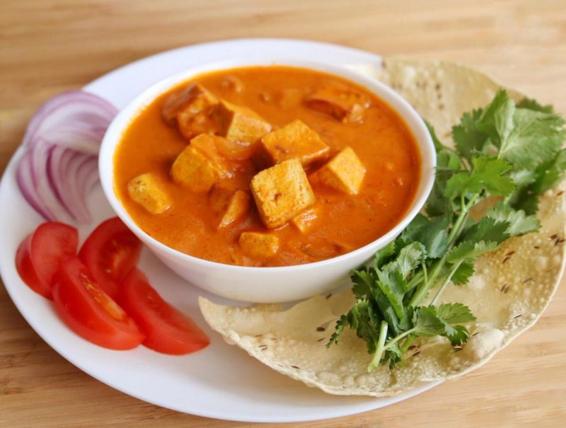 Vegan paneer tikka masala on dish with papadum